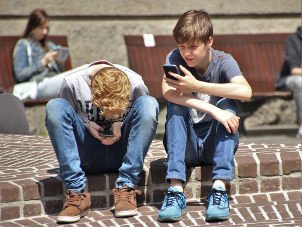 tween boys on cellphones - public domain image from https://www.pexels.com/photo/2-boy-sitting-on-brown-floor-while-using-their-smartphone-near-woman-siiting-on-bench-using-smartphone-during-daytime-159395/
