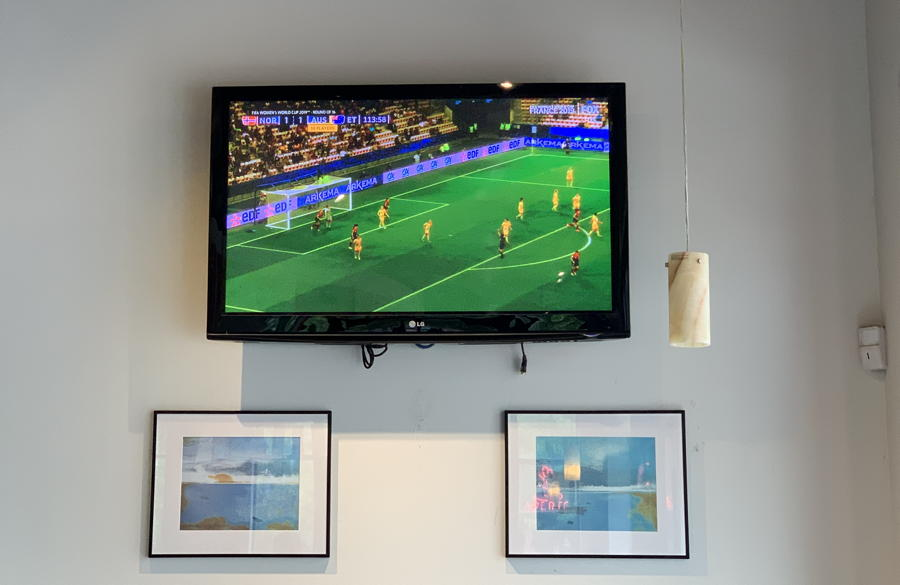 tv on wall, showing world cup soccer