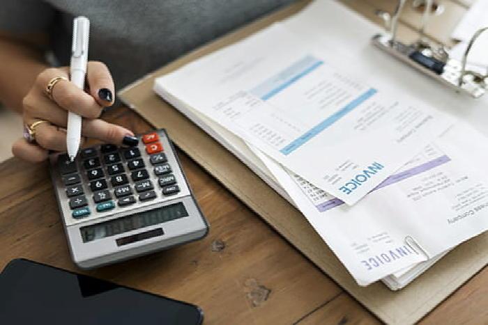 woman calculating calculator clipboard